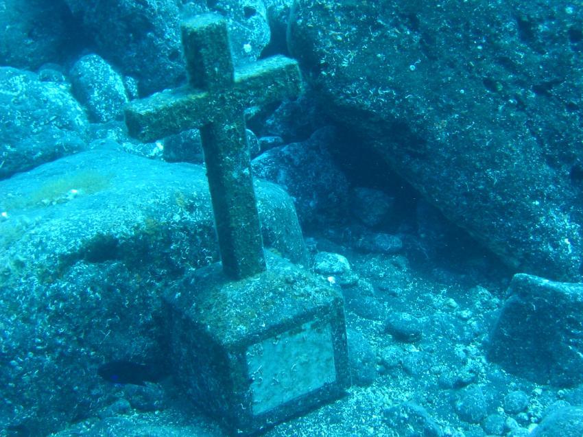 Gedenktafel mit Kreuz unter Wasser